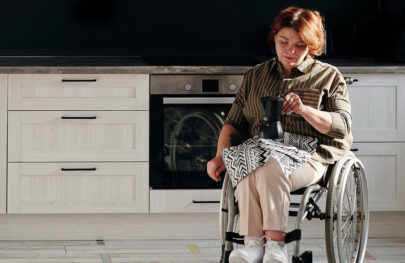Woman in wheelchair in kitchen holding coffee pot