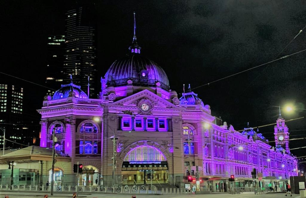 Flinders St Station in Melbourne lit by purple lights.